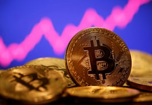 A representation of virtual currency Bitcoin is seen in front of a stock graph in this illustration.