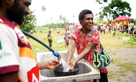 A woman washes her hands at a market in East New Britain province, Papua New Guinea