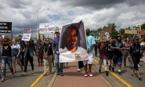 Protesters hold an image Philando Castile on Sunday in St Anthony, Minnesota.