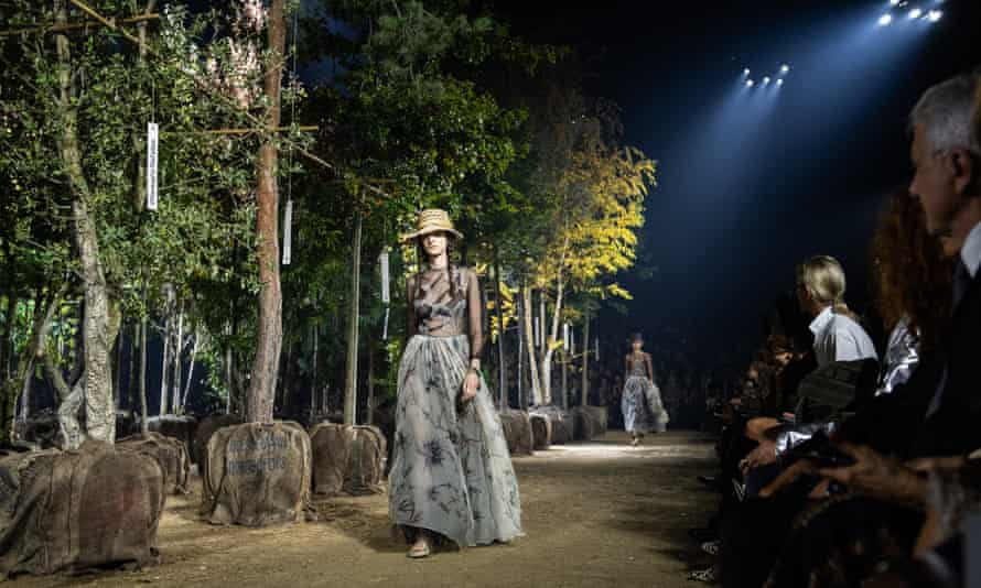 A fashion show takes place among trees.