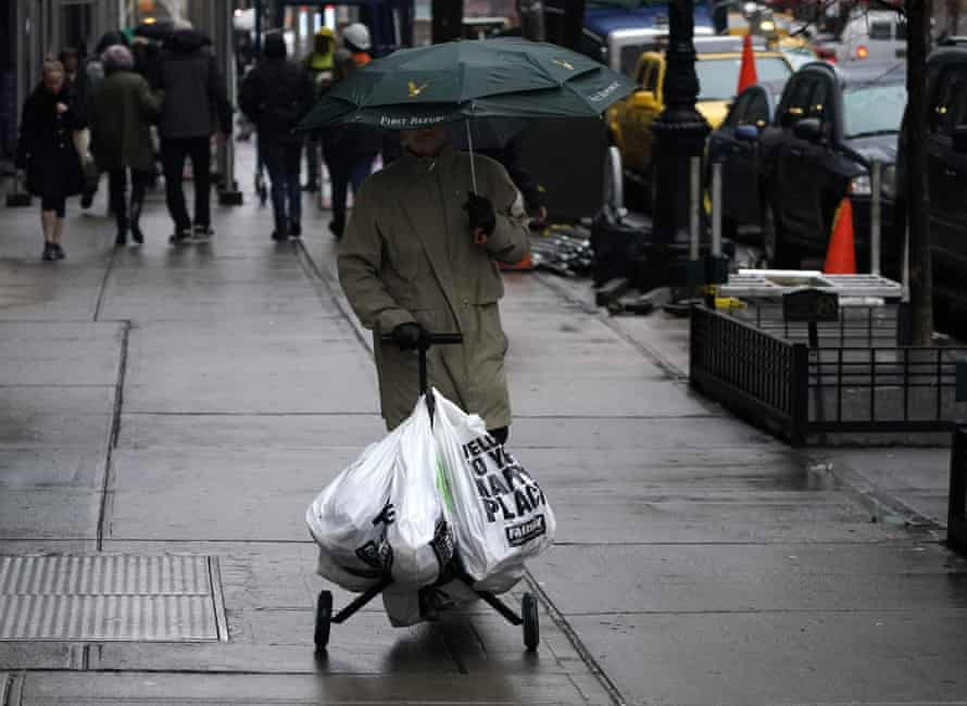 A person with groceries in plastic bags walks on the Upper East Side in New York on 28 February 2020