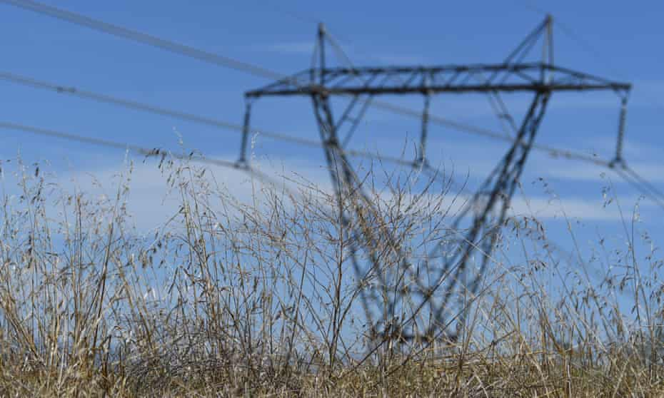 An electricity pylon in a field of grass