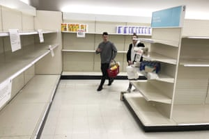 Shoppers walk through nearly-empty shelves in a Target store in Olympia, Washington, US