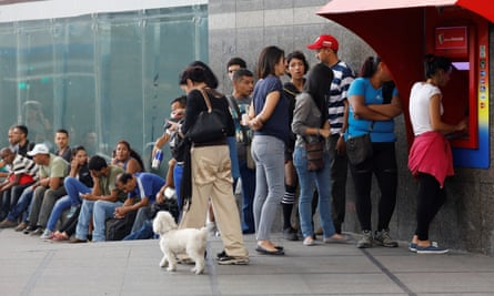 People line up to withdraw cash from an ATM outside a Banco de Venezuela in Caracas.