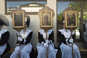 Women in traditional costumes hold pictures of saints during the eucharistic celebration of the feast of Corpus Christi in Appenzell, Switzerland