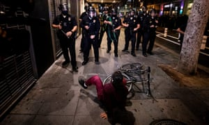 A woman falls off her bicycle as police officers prevent protesters from entering a street in Los Angeles