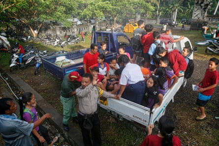 Children are evacuated from the area around Mount Agung.
