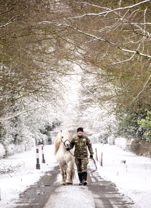 A staff member from Whatton Manor Stud leads a horse down icy paths in the Vale of Belvoir, Nottinghamshire.
