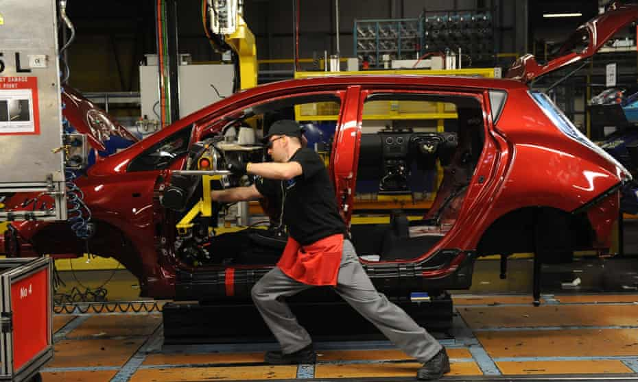 A dashboard being fitted on a car manufacturing line.