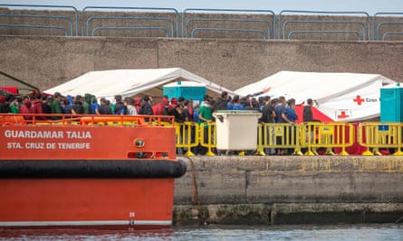 People rescued from different boats remain in the port of Arguineguín on the island of Gran Canaria, while being cared for by police and the Spanish Red Cross.