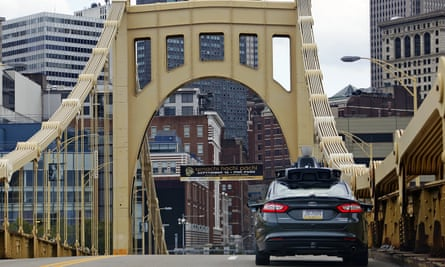 A self-driving Uber car drives navigates one of Pittsburgh's many bridges.