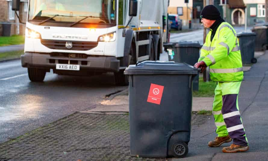 A refuse worker collects one of the wheelie bins sporting the 'waster' emoji.