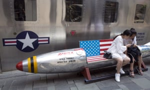 Chinese women sit on a rocket-shaped bench with an American flag in a US clothing store in Beijing, China.