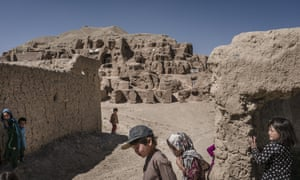 Afghan children play in front of caves where they live at the old city of Bamiyan in Afghanistan