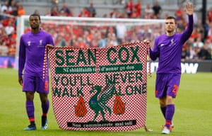 Georginio Wijnaldum, left, and Andrew Robertson carry a flag in support of Sean Cox in August.