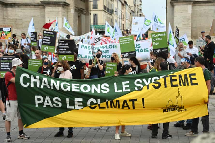 A man holds a banner reading 'Change the system not the climate'