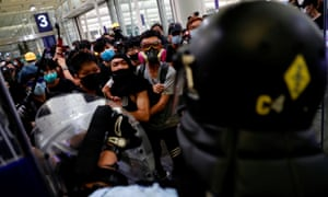 Protesters face riot police during a demonstration at Hong Kong's international airport on 13 August 2019