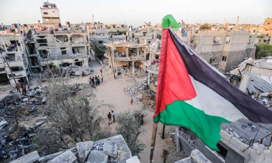 A Palestinian flag atop a destroyed building in Beit Hanoun, Gaza, 26 May 2021.