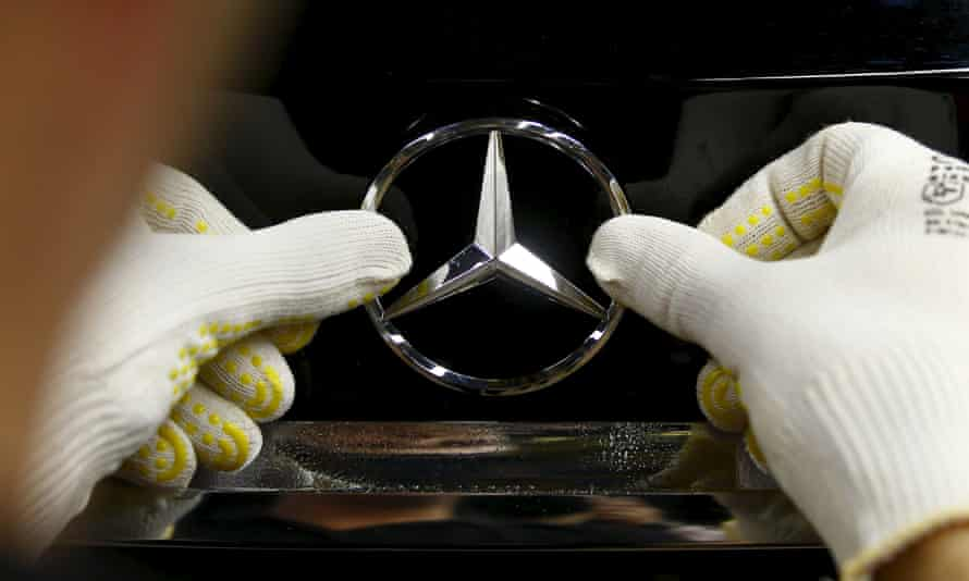 mercedes badge being put on a car by a human