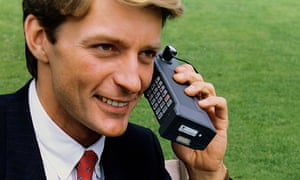 a 1980s yuppie on a huge mobile telephone
