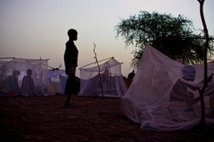 A young boy stands by the mosquito net that forms his family's only shelter at night