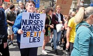 """A nurse holds a poster saying """"NHS nurses against Brexit lies"""" at a protest in London in 2016"""