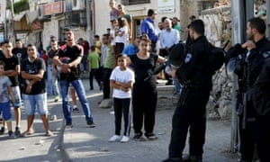 Palestinians look on as Israeli police set up a checkpoint in the east Jerusalem neighbourhood of Ras al-Amud.