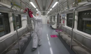 An employee disinfects handles as a precaution against the coronavirus on a subway train at a subway station in Seoul, South Korea.