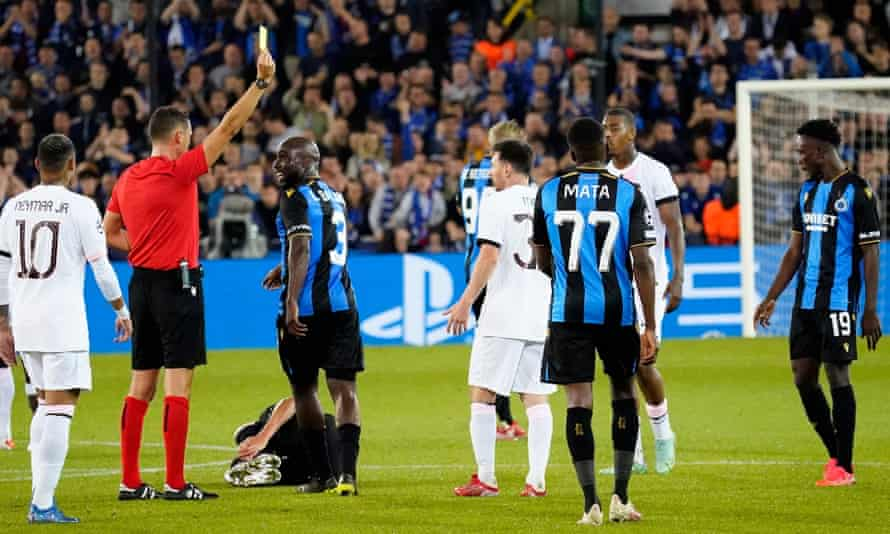 Lionel Messi is booked during PSG's 1-1 draw at Club Brugge