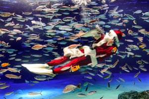 A diver dressed as Santa Claus performs inside a tank at an aquarium in Tokyo, Japan