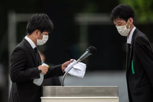 Attendants clean a microphone before a speech by Japan's prime minister, Shinzo Abe