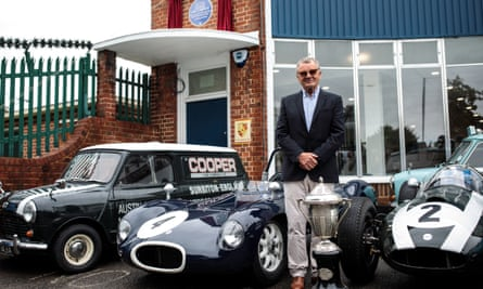 Mike Cooper, son of carmaker John Cooper, poses with historic cars at the former Cooper Car Company works, newly adorned with a blue plaque.