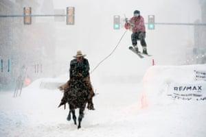 Leadville, Colorado: Jeff Dahl races down Harrison Avenue while skier Jason Dahl takes the final jump in a skijoring race