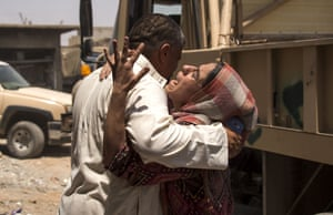 A man comforts a relative who fled the fighting between Iraqi government forces and Islamic State militants in Mosul's old city.
