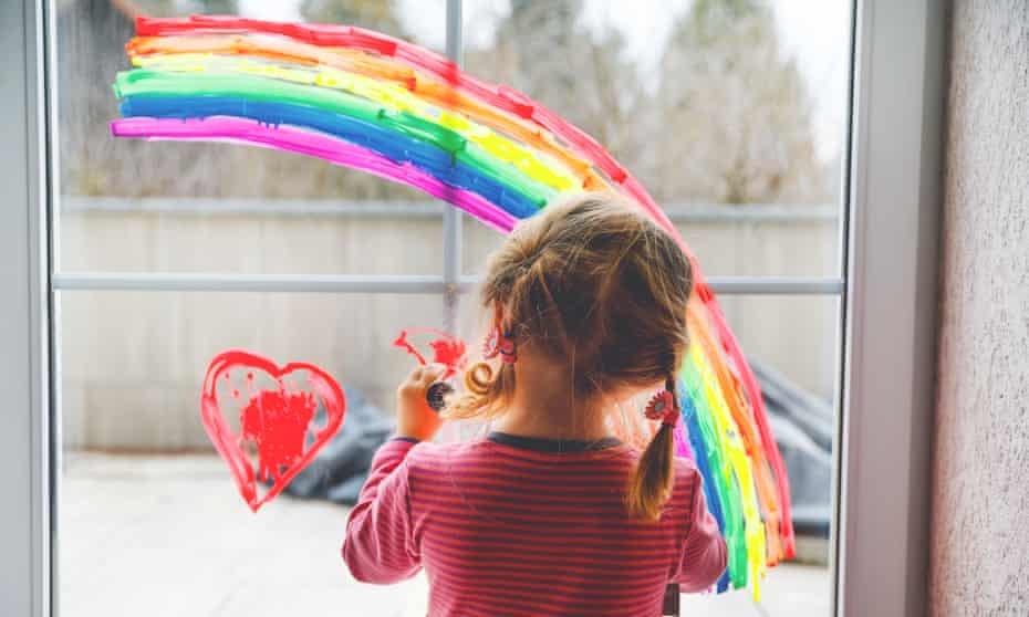 Child painting a rainbow on a window in a home.