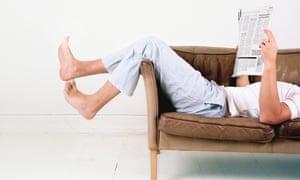 Man lying on sofa with newspaper