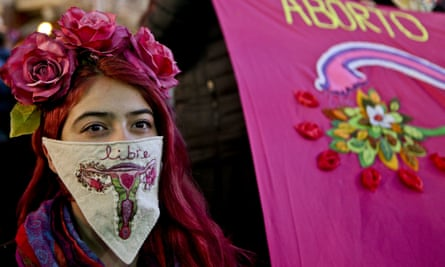 """A woman wearing a handkerchief embroidered with a uterus and the Spanish word for """"free"""" participates in a pro-abortion march in Santiago, Chile"""