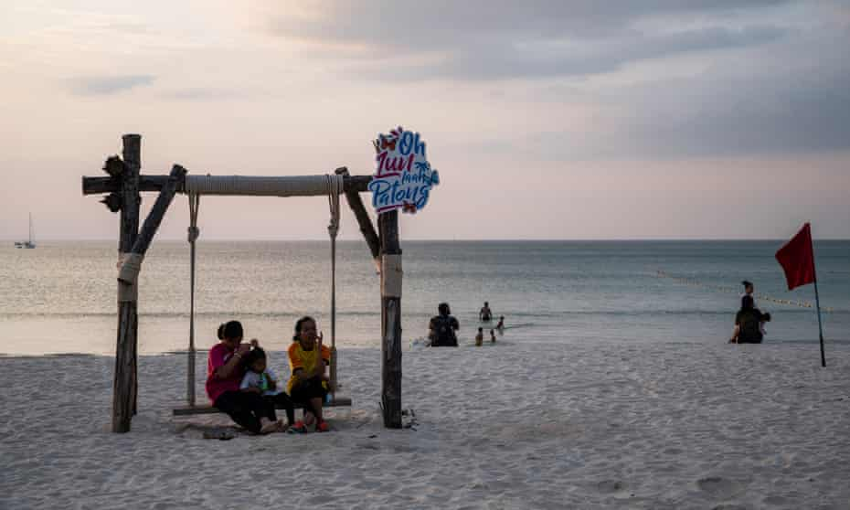 A small group of people gather at a relatively empty Patong Beach in Phuket