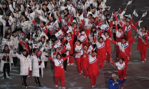 North Korean and South Korean delegations wave their flags along with the Unified Korea flag during the closing ceremony of Pyeongchang 2018 .