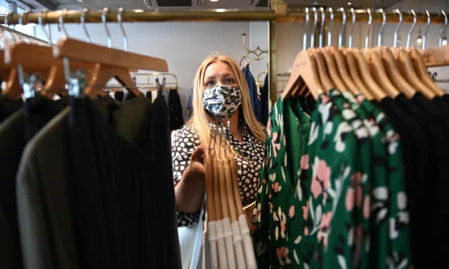 A store assistant prepares a display of clothes in a shop in London