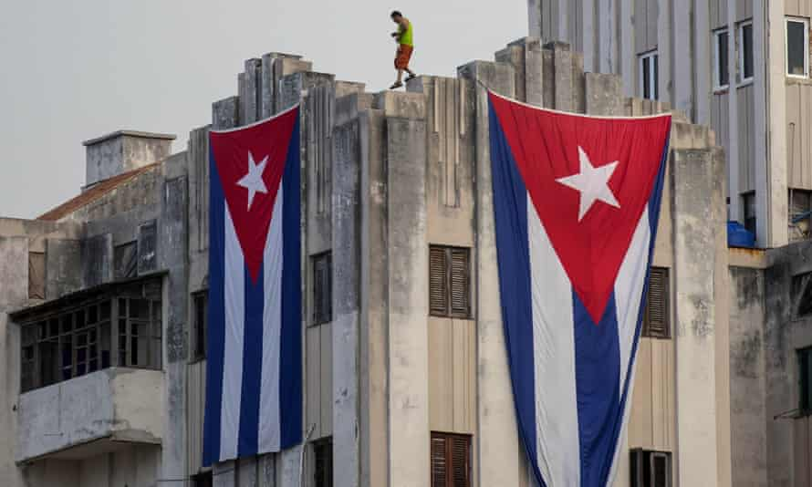 A man walks along the ledge of a building after hanging two giant Cuban flags, next to the US embassy in Havana.