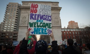 People hold signs during a protest in New York against Trump's refugee ban