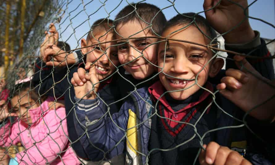 Syrian refugee children peep through the fence of a former basketball court that is now their school playground in a refugee camp near Taalabaya in the Bekaa Valley.
