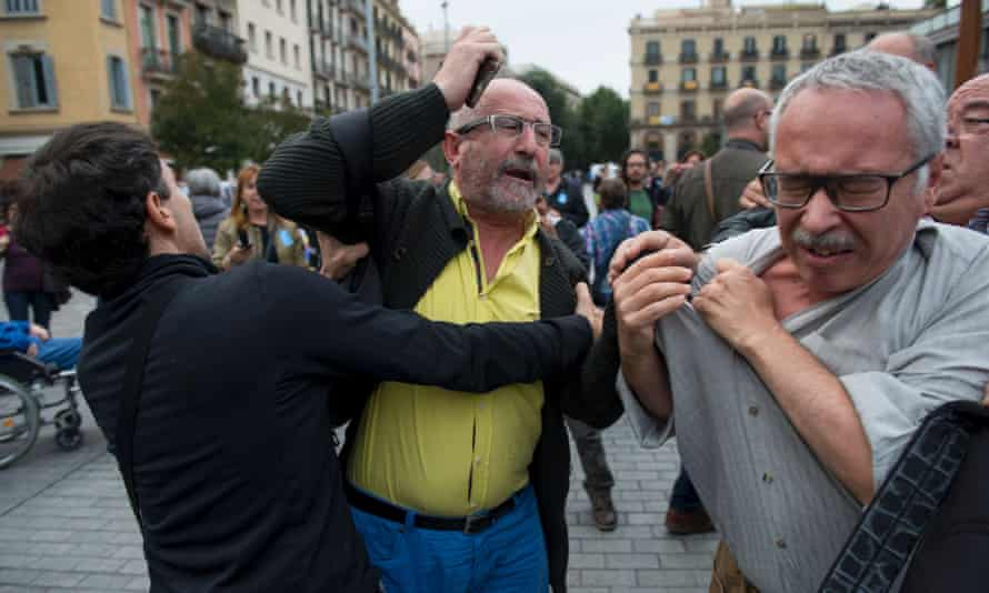 A man is held back as he tries to hit another during the installation of the Franco exhibition outside the Mercat de Born cultural centre in Barcelona.