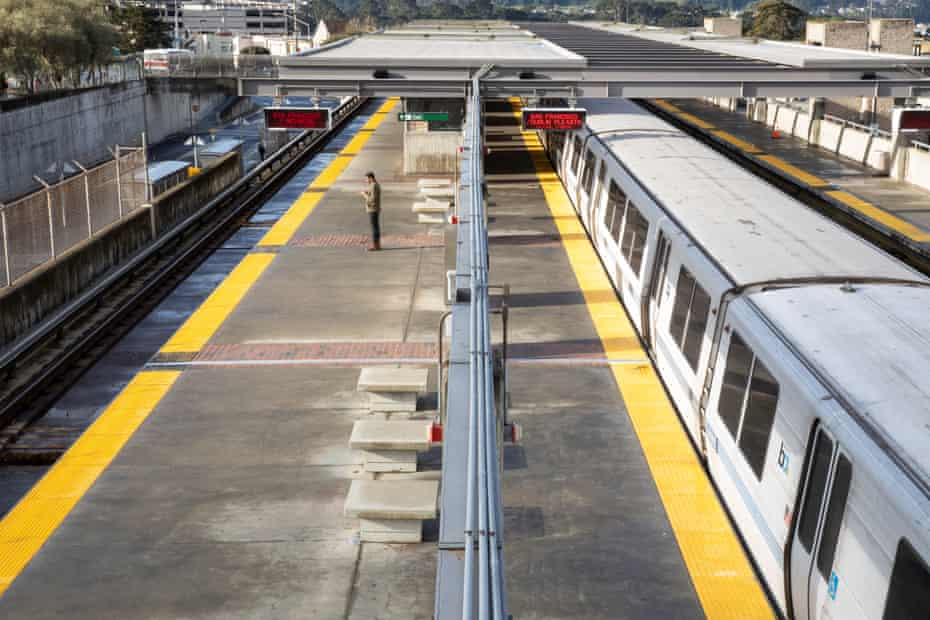 A lone commuter waits for a San Francisco-bound Bart train at an empty station south of San Francisco, California.