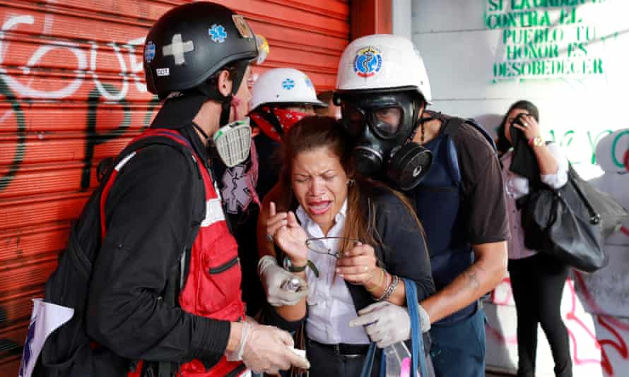 A woman overcome by tear gas receives assistance from volunteers during a rally against President Maduro's government in Caracas