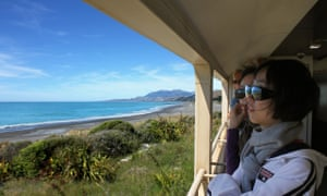 Tourists looking out from a viewing carriage on the Coastal Pacific