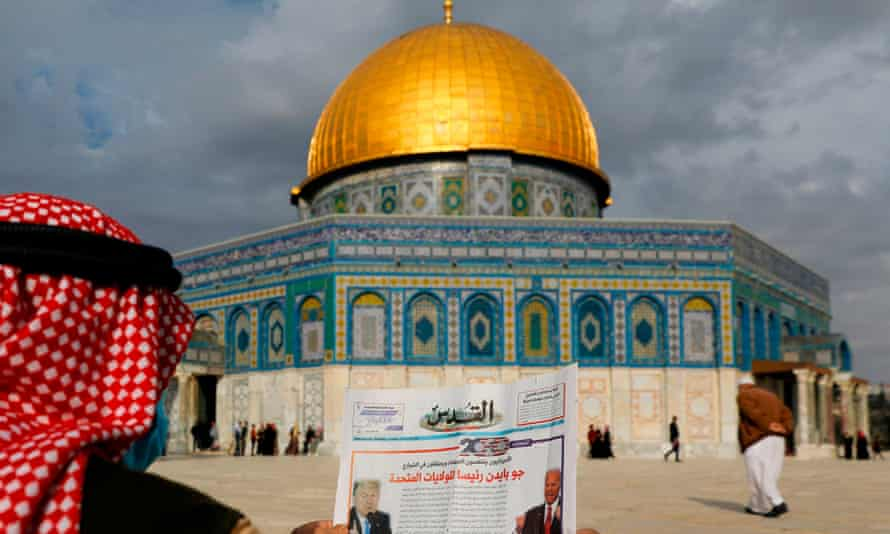A Palestinian man reads news about the US election in front of the Dome of the Rock in the al-Aqsa mosque compound