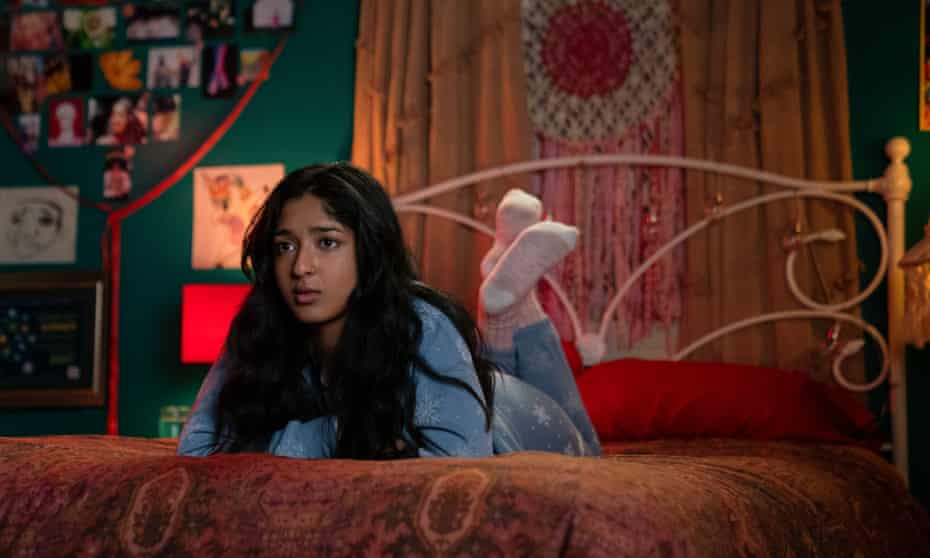 Maitreyi Ramakrishnan, as Devi, lays on her bed in a scene from Never Have I Ever