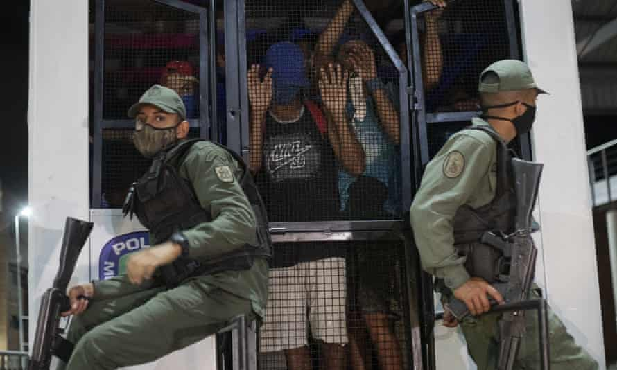 Venezuelan police guard men who were detained for not complying with Covid-19 regulations by breaking curfew or attending block parties in the Petare neighborhood of Caracas this month.